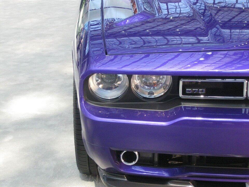 The front angle of a purple Dodge Challenger.