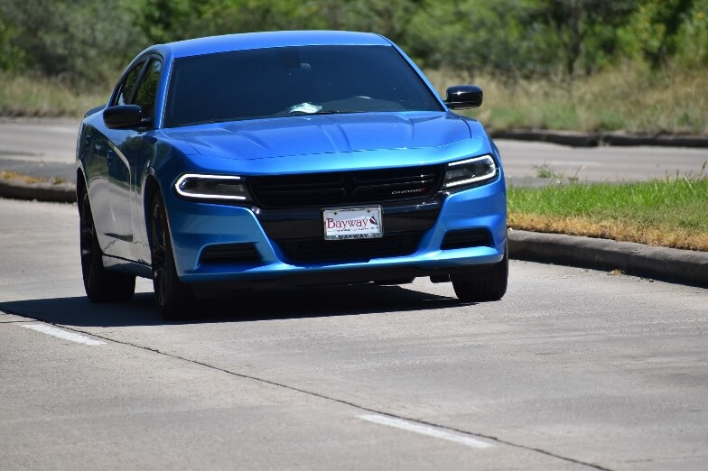 A blue Dodge Charger with tinted windows on a road
